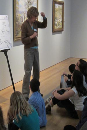 In teaching about comparison and contrast, docent Alice Gilbert shows students two different paintings that have horses as the main subject.