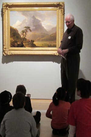 Jerry Mears, volunteer docent, talks to the third-graders about why this painting shown here is one of his favorites.