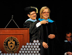 Dr. Olivarez officially named Ellen Satterlee an Honorary Doctor of Public Policy by laying the blue doctoral hood over her shoulders during graduation ceremonies in Aquinas's field house.