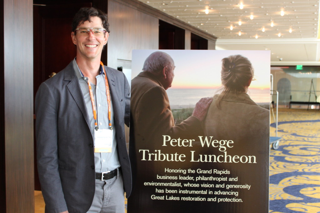 Andrew Goodwillie stands beside a photograph of his late grandfather Peter M. Wege and Terri McCarthy, Vice-President of programming for The Wege Foundation,  at the Healing Our Waters Conference's luncheon honoring Mr.  Wege. The accompanying   tribute video was shown at the luncheon.